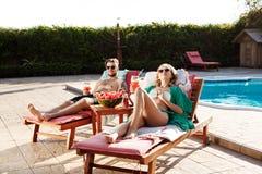Les amis souriant, cocktails potables, se trouvant sur des cabriolets s'approchent de la piscine Photos stock