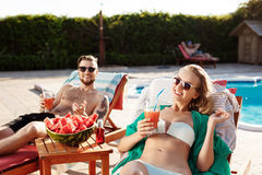 Les amis souriant, cocktails potables, se trouvant sur des cabriolets s'approchent de la piscine Photographie stock