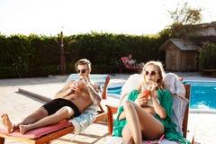 Les amis souriant, cocktails potables, se trouvant sur des cabriolets s'approchent de la piscine Images stock