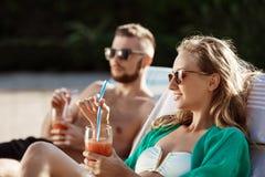 Les amis souriant, cocktails potables, se trouvant sur des cabriolets s'approchent de la piscine Photo libre de droits