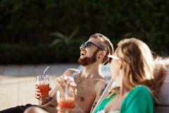 Les amis souriant, cocktails potables, se trouvant sur des cabriolets s'approchent de la piscine Images libres de droits