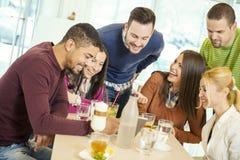 Les amis souriant et s'asseyant dans un café, café potable et apprécient Photo stock