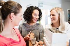Les amis sur des achats se déclenchent discutant des sandales et achetant des chaussures Photographie stock libre de droits