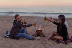 Les amis sur la plage font la fête l'alcool potable et font tinter des verres Images libres de droits