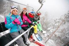 Les amis sur le remonte-pente montent sur la montagne neigeuse Photos stock