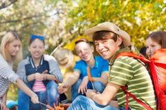 Les amis sur le terrain de camping avec des saucisses colle dans la forêt Photographie stock libre de droits