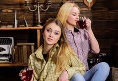 Les amis sur les visages calmes dans le plaid vêtx la détente Filles détendant et buvant du vin chaud Amis dans des équipements o Photo stock