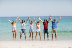 Les amis tenant des mains avec des bras ont augmenté à la plage Photo libre de droits