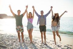 Les amis tenant des mains avec des bras ont augmenté sur le rivage à la plage Image stock