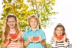 Les amis tiennent la pastèque et la consommation ensemble dans la rangée Image libre de droits