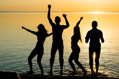 Les amis, les types et les filles, étudiants dansent au backgrou de coucher du soleil Photos stock