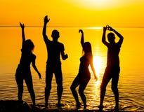 Les amis, les types et les filles, étudiants dansent au backgrou de coucher du soleil Image stock