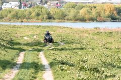 Les amis voyagent en vélo de quadruple le long de la berge image libre de droits