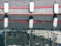 Les amortisseurs de bateau accrochant sur le conseil se reflètent dans l'eau Photos libres de droits