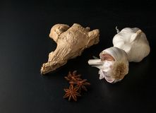 Les ampoules de l'ail, noix de muscade, anis se tient le premier rôle sur un fond noir photo libre de droits