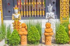 Les anges d'or et blancs et les petites statues oranges de moines sont acte payant le respect à l'accueil au temple bouddhiste pu photo stock