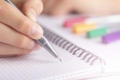 Les années de l'adolescence écrivent le stylo jaune noir dans un carnet à carreaux photo libre de droits