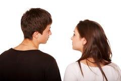 Les années de l'adolescence couplent regarder quelque chose et parler. Vue arrière Image libre de droits
