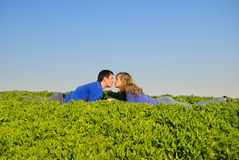 Les années de l'adolescence embrassent dans une herbe Photographie stock