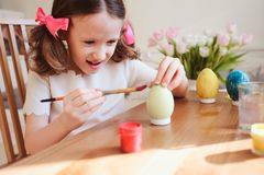 Les 7 années heureuses badinent la fille peignant des oeufs de pâques Préparations de métier et de vacances de Pâques Images libres de droits