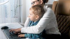 Les 2 années mignonnes de garçon d'enfant en bas âge s'asseyant sur des mères enroulent le travail dans le bureau Photographie stock libre de droits