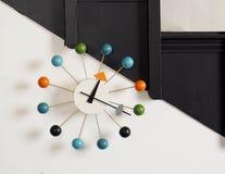 Les années '60 ont coloré la rétro horloge sur un fond noir et blanc de mur Image stock