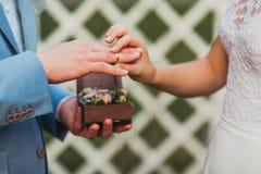 Les anneaux d'échange de nouveaux mariés, marié met l'anneau sur la main du ` s de jeune mariée Photographie stock libre de droits