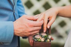 Les anneaux d'échange de nouveaux mariés, marié met l'anneau sur la main du ` s de jeune mariée Photos libres de droits