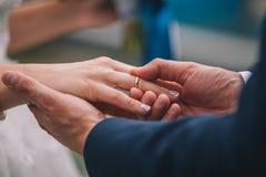 Les anneaux d'échange de nouveaux mariés, marié met l'anneau sur la main du ` s de jeune mariée Photos stock