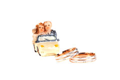 Les anneaux de mariage à côté d'un chocolat de jouet usinent l'isolement sur un whi Photographie stock