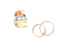 Les anneaux de mariage à côté d'un chocolat de jouet usinent l'isolement sur un whi Photographie stock libre de droits