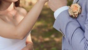 Les anneaux de mariage d'échange de jeunes mariés sur un fond de nature verte Le marié met l'anneau sur le bras de banque de vidéos
