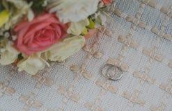 Les anneaux de mariage d'or blanc se trouvent sur une couverture beige, un bouquet nuptiale photo libre de droits