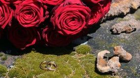 Les anneaux de mariage d'or ont élégamment arrangé devant le bouquet nuptiale Image stock
