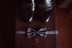 Les anneaux de mariage d'or se trouvent devant arc bleu derrière les chaussures en cuir Images stock
