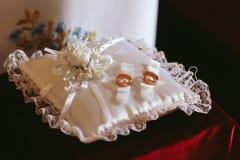 Les anneaux de mariage d'or se trouvent sur l'oreiller en soie blanc Image libre de droits