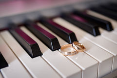 Les anneaux de mariage d'or se trouvent sur les clés de piano photo stock
