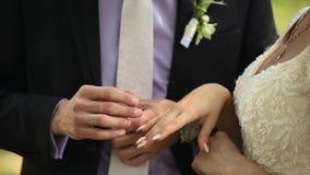 Les anneaux de mariage d'usage de jeunes mariés entre eux banque de vidéos