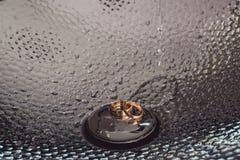 Les anneaux de mariage dans un chrome ont plaqué le lavabo Réflexions de lumière le fond 3d rendent éclabousse l'eau blanche Photo stock