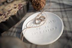 Les anneaux de mariage en or blanc, soucoupe en argile avec le mot toujours doivent être votre ami Image libre de droits