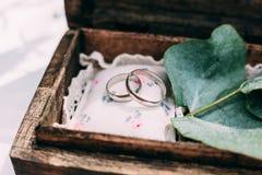 Les anneaux de mariage de l'or blanc dans une boîte en bois ont rempli de la mousse, Image stock