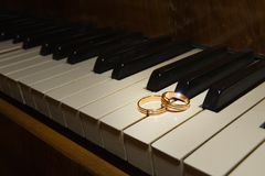 Les anneaux de mariage se trouvent sur des clés noires et blanches du piano Photos libres de droits