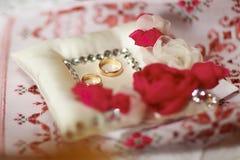 Les anneaux de mariage se trouvent sur l'oreiller avec les cristaux et la rose en soie de rose Images stock