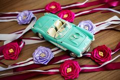 Les anneaux de mariage se trouvent sur le capot d'un convertible de jouet images stock