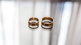 Les anneaux de mariage se trouvent sur le verre et montré dans lui Image libre de droits