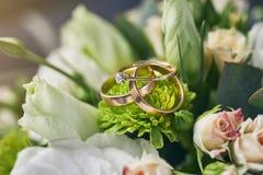 Les anneaux de mariage se trouvent sur un beau bouquet en tant qu'accessoires nuptiales images stock