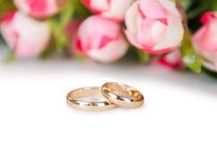 Les anneaux et les fleurs de mariage d'isolement sur le fond blanc Photos libres de droits