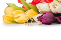 Les anneaux et les fleurs de mariage d'isolement sur le fond blanc Photos stock