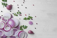 Les anneaux ont coupé en oignons rouges avec des herbes et des épices sur une table en bois blanche légumes photographie stock libre de droits
