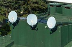 Les antennes paraboliques, antennes de satellite ont monté sur un toit vert Photographie stock libre de droits